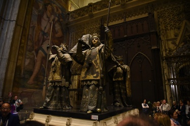 Columbus made four trips to the New World, which he always thought was Asia, during his life. He kept traveling after he died, being buried in northwest Spain, the Dominican Republic, Cuba, and finally Seville. Here he is being carried by pall bearers representing Castile, Aragon, León, and Navarre - four regions of Spain.